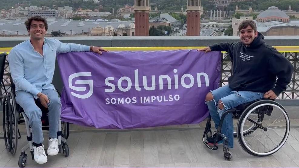 Dani Caverzaschi y Martín de la Puente sujetan una bandera de Solunion